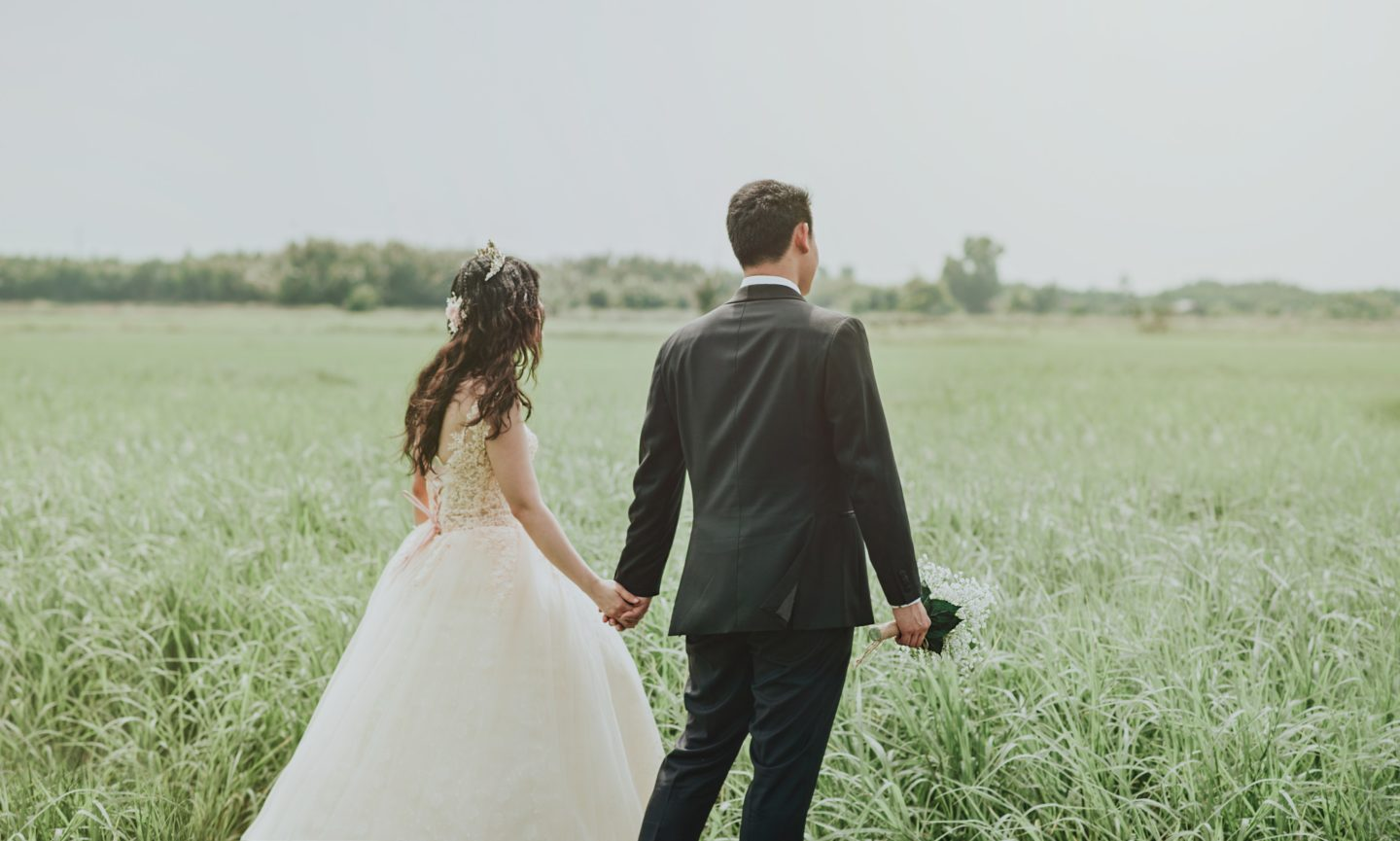 Husband guiding his wife through a field.