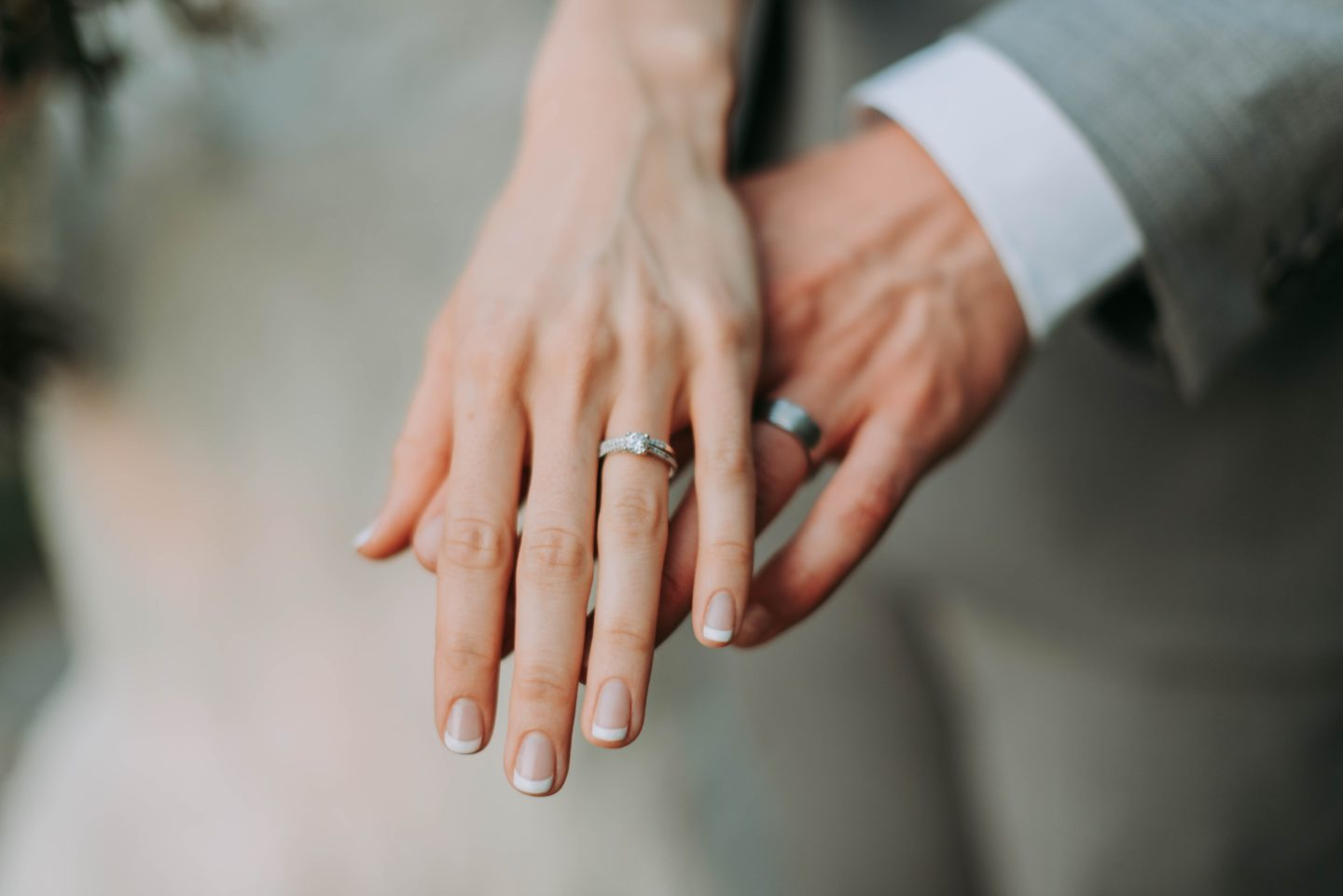 Holding hands while showing off wedding bands