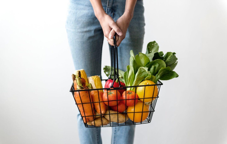 Woman holding basket of fresh veggies.