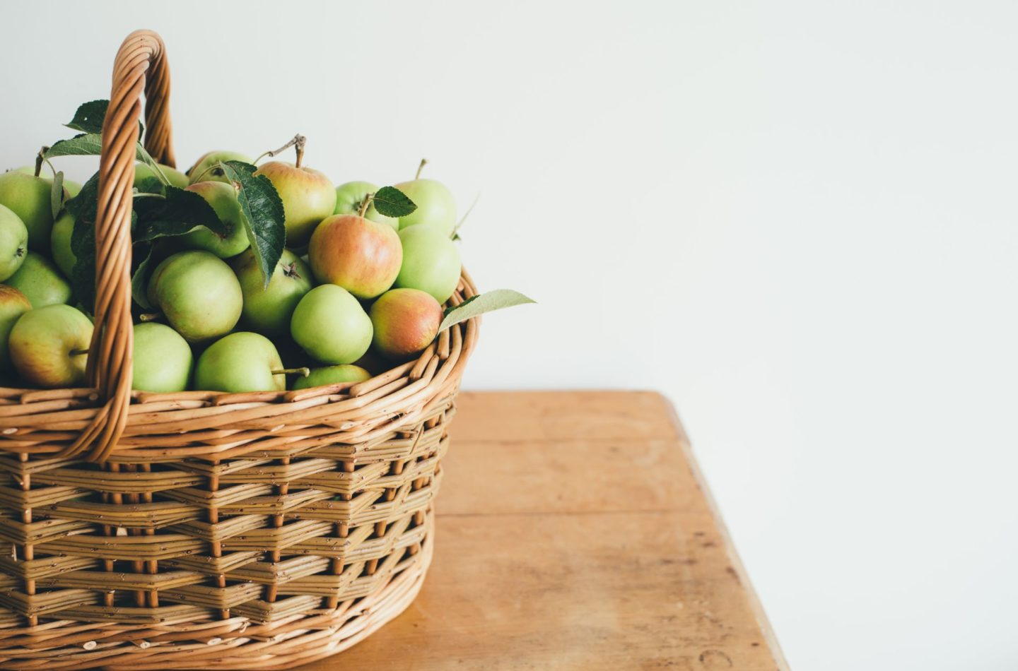 Basket full of green apples on a wooden table.